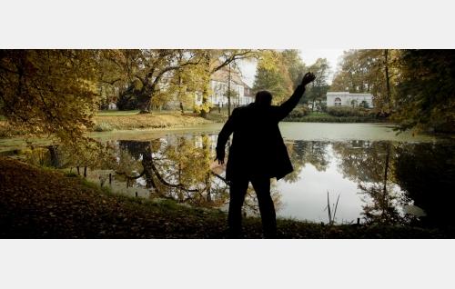 Theo (Hannu-Pekka Björkman) suunnittelee unelmiensa taloa saksalaisen linnan puutarhassa. ©  Rax Rinnekangas.