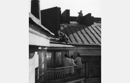 Komisarion apulainen Toivo Virta (Matti Ranin) kiipeää kameroineen peltikatolla Pohjoisen Rautatiekadun ja Nervanderinkadun kulmauksessa. Parvekkeella ovat vas. komisario Palmu (Joel Rinne), etsivä Kokki (Leo Jokela) ja murharyhmän etsivä (Tauno Söder). Katolla oikealla Paavo Hukkinen murharyhmän etsivänä.