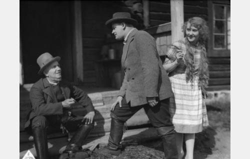 Yli-Iimin isäntä (Emil Lindh) ja hänen tyttärensä Emmi (Ellen Sylvin) kotitalonsa portailla seurassaan Seipin Matti, Emmin sulhanen (Gunnar Calenius).