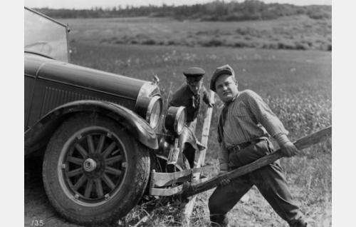 Matka on katkennut. Työpäällikkö Männistö (Paavo Costiander) kampeaa kuljettajan kanssa autoa ojasta.