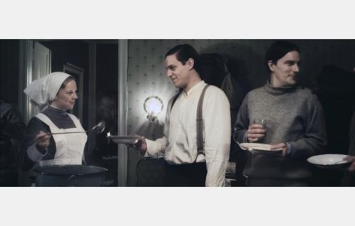 Aina Gadolin (Alma Pöysti) jakaa ruokaa valkokaartilaisille Eccu Widingille (Jakob Öhrman) ja Lonni Tollet'lle (André Wickström). Kuva: Helsinki-filmi Oy.