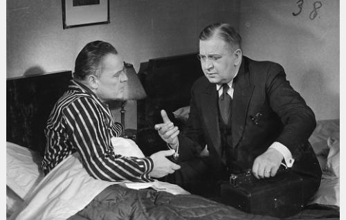 Tohtori Katajisto (Uuno Montonen, oik.) tarkistaa tuomari Pakkolan (Yrjö Tuominen) kunnon.