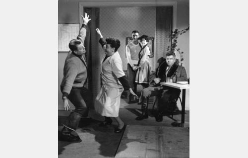 Eemeli on intoutunut twistaamaan kahvibaarinomistaja Bertta Piiparisen (Siiri Angerkoski) kanssa. Taustalla nuoripari Ilmari Ilonen (Ismo Kallio) ja Ilona Pösö (Pirkko Mannola), oikealla istuu yrmeä Petteri Pösö (Risto Mäkelä).