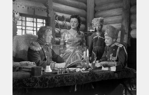 Siperialaisen vankileirin johtaja, venäläinen kenraali (Sven Relander) ja hänen puolisonsa, kreivitär Marina (Laila Jokimo). Kasakat oikealla tunnistamattomia.