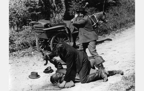 Hallin Santtu-renki (Harri Sinijärvi) makaa maassa, postinkuljettaja Matti Alatalo (Aarne Laine) vääntää pistoolia hänen kädestään. Hallin Janne (Helge Herala) antamassa postinkuljettajalle surmaniskua.