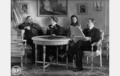 Kauppaneuvos Merthenin perhe: Albert Merthen (Yrjö Tuominen, vas.), Magdaleena Merthen (Henny Waljus), Verna Gavelius, o.s. Merthen (Ester Toivonen) ja insinööri Thure Gavelius (Joel Rinne).