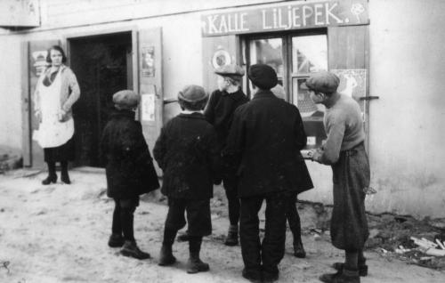 """Liljepekin Neilikka, """"korttelin lempeä valtiatar"""" (Helinä Svensson-Timari) kauppansa ovella."""