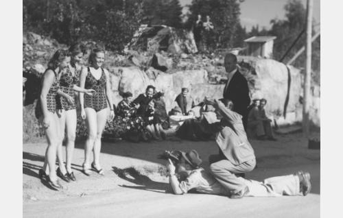 Säveltyttöjä (keskellä Eija Londén) kuvataan. Maassa pitkällään kuvaaja Olavi Gunnari vieterikäyttöisine Eyemo-kameroineen, kyykkysillään hänen päällään ohjaaja Nyrki Tapiovaara rajaa käsillään kuvakulmaa. Tapiovaaran takana Antti Halonen.