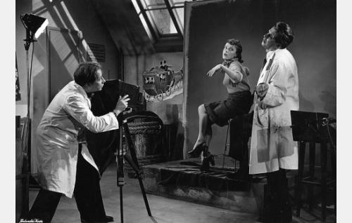 Sukkatehtaan mainosvalokuvaaja (Joel Asikainen, vasemmalla) ja mainosmies (Tarmo Manni) opettavat Eevaa (Liisa Tuomi) poseeraamaan.