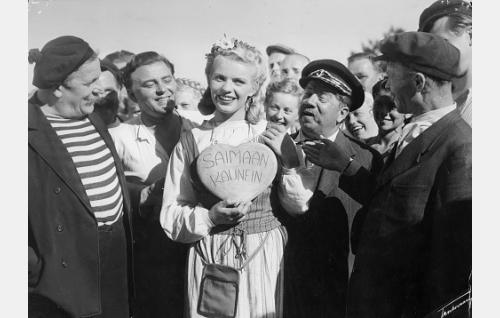 """Susanna, """"Saimaan kaunein"""" (Tuija Halonen) ihailijoidensa ympäröimänä. Vasemmalta laivamiehet Rääveli (Uuno Laakso), Jantsu (Väinö Luutonen) ja Pekka (Olavi Virta), oikealla kippari (Kalle Viherpuu) ja huvimenojen ohjaaja (Kaarlo Karppanen) takanaan laivamies Venskinpoika (Hannes Häyrinen)."""