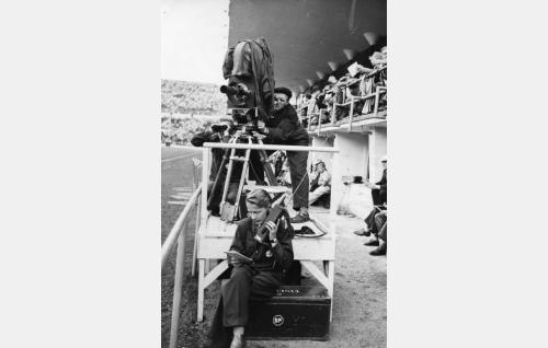 Kuvausryhmä valmiusasemissa Olympiastadionilla. Cinephon-kamerassa on 300 mm:n optiikka, kameran takana kuvaaja Erkki Imberg. Yhteyttä hoidettiin mm.kiikarin ja radiopuhelimen välityksellä. Kameran päällä on sadesuoja.