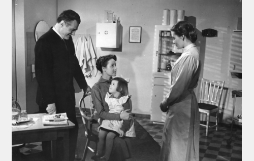 Lääkäri Olavi (Tauno Palo) ja lastenkodin johtajatar (Irma Seikkula) seisovat. Pikku-Eeva (Ulla Nuorvala) sylissään istuu Olavin vaimo Eeva (Eeva-Kaarina Volanen).
