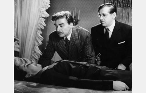 Tohtori Dahlberg (Pentti Irjala, oik.) ja komisario Palmu (Joel Rinne) tutkivat rouva Alli Rygseckin (Aino Mantsas) ruumista.