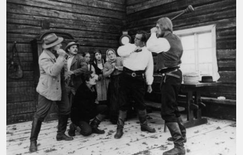 Puukkoja ja puntareita Haapalan tuvassa: Hossian Simo (Kalle Kaarna), Mäkkylän Mikko (Eero Leväluoma) edessään polvistuneena Koljon Eero (Helge Ranin), Haapalan ottotytär (Saara Ranin), Haapalan Helka (Rakel Tarpila), Haapalan emäntä (Lyyli Eriksson), Haapalan Hannu (Uuno Eskola) ja Haapalan isäntä (Martti Elomaa).
