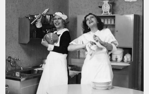 Rouva Anderssonin täysihoitolan iloiset keittiöhengettäret, palvelijatar (Greta Pitkänen) ja rouvan miesvainajan veljentytär Aune Andersson (Saimi Tuominen).
