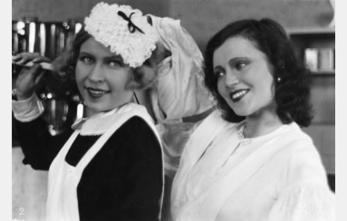 Rouva Anderssonin täysihoitolan palvelijatar (Greta Pitkänen) ja tytär Aune Andersson (Saimi Tuominen) keittiöpuuhissa.