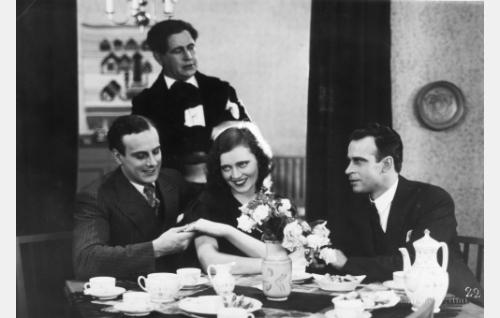"""Toivo (Thure Bahne) on ihastunut Auneen (Saimi Tuominen), oikealla hänen huonetoverinsa Unto (Toivo Pohjakallio) ja taustalla kilpakosijansa """"Toreadoori"""" Kiljunen (Georg Malmstén)."""