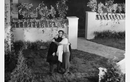 Varpu Kyyhkynen (Ella Eronen) ja Reino Kiljunen (Georg Malmstén) lemmekkäässä kohtauksessa täysihoitolan puutarhassa.
