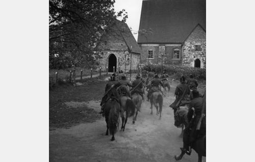 Kasakat lähestyvät kirkkoa. Jakso kuvattiin Hattulassa, ja kasakoina avustivat Parolannummella leiriä pitävät kadetit.