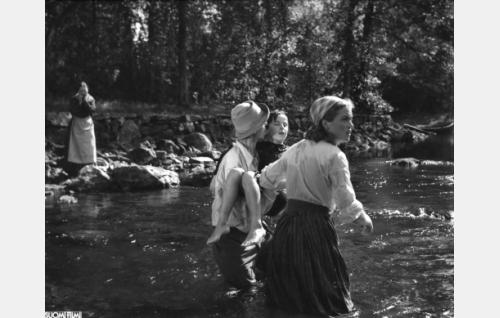 Pikku-Leena (Eliina Brandt) on pelastettu virrasta. Leenaa kantaa Pertteli-vaari (Väinö Hellén), oikealla Niskalan Hanna (Irma Seikkula). Vasemmalla rannalla kauhistunut Eetla-emäntä (Aino Lohikoski).
