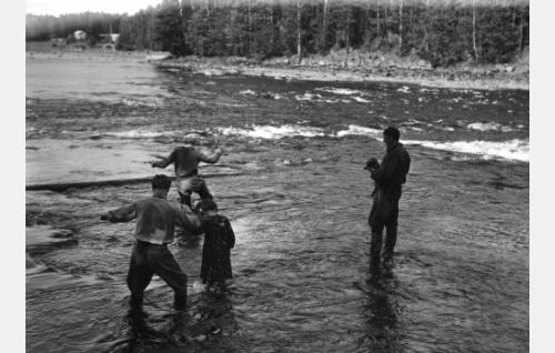 Olavi Reimas taluttaa Eliina Brandtia virran pyörteissä tapahtuvan kohtauksen ottopaikkaan. Edellä kahlaa ohjaaja Valentin Vaala. Oikealla seisoo kuvaaja Björn Soldan mykkä Eyemo-kamera kädessään.