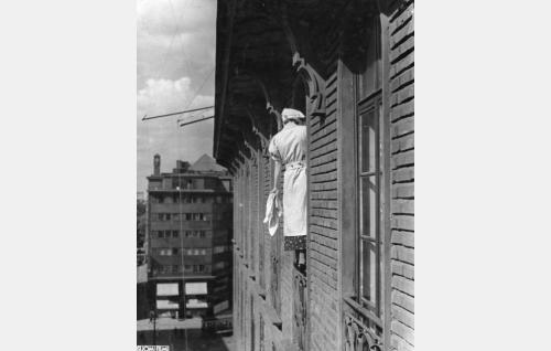 Juurakon Hulda (Irma Seikkula) pesee tuomari Soratien olohuoneen ikkunoita Kaisaniemenkatu 5:ssä.