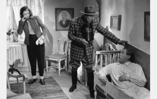 Pääkonna Henry Williams (Ville Salminen) uhkaa aseella Pekka Lipposta (Reino Valkama), vasemmalla Liisa (Tiina Rinne).