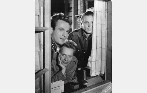 Luutnantti Naula (William Markus), kapteeni Veikko Saarto (Kullervo Kalske) ja ikkunalautaan nojaava sotamies Taavetti Hurskainen (Sakari Halonen).