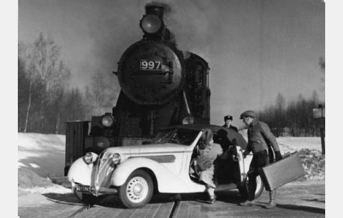 Yrjö Haara (Joel Rinne) on pysäyttänyt junan ja noutanut sieltä Ulla Järvisen (Lea Joutseno). Taustalla junailija (Urho Westman).