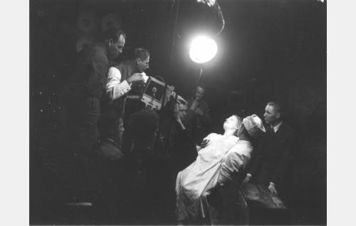 Työkuva: Kuisma (Tauno Brännäs) on pelastanut Helinän (Iris Knape-Jäderholm) hukkumasta koskeen. Askania-kameran takana ojaaja Kalle Kaarna (vas.) ja kuvaaja Josef Dietze, äärimmäisenä oikealla toinen kuvaaja ja apulaisäänittäjä Yrjö Nyberg.