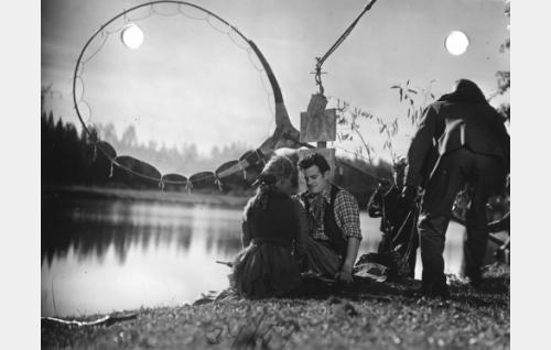 Ansa Ikosen ja Tauno Palon kohtausta kuvataan. Auringonvaloa pehmennetään harsokankaaan avulla, näyttelijöiden yläpuolella riippuu tuulisuojattu mikrofoni.