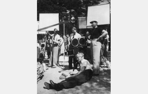 Kuvausryhmä Hangon hiekkarannalla kesällä 1939. Ohjaaja Risto Orko seisoo oikealla , Debrie-kameran takana B-kuvaaja Eino Heino, vasemmalla kuvausryhmän jäsen Komppa ja edessä pitkällään Charlie Bauerin tulkki, Helsingin Venäläisen Klubin hovimestari Georgi Goubtschenko.