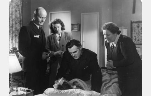 Sängyn ympärillä lääkäri (Wilho Ilmari), sairaanhoitajatar Rauni Verkkola  (Eila Peitsalo), kamreeri Aarno Harjus   (Tauno Palo) ja kotiapulainen Anna (Elna Hellman). Sängyssä pikku potilas Annika (Annika Sipilä).
