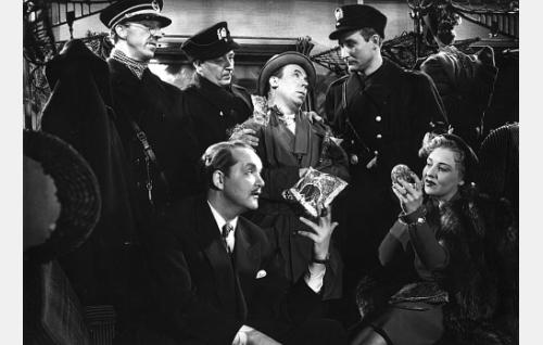 Vasemmalla seisoo junailija Samuli Saastamoinen (Esa Pakarinen), junapoliiseina Kauko Laurikainen ja Mauno Enroth, heidän välissään Läski-Leevi (Masa Niemi). Istumassa konnien pomo  Kulaus-Ramperi (Leo Lähteenmäki) ja tämän heila Töikän Taimi (Irja Rannikko).