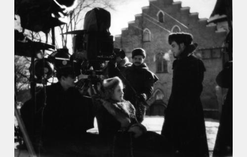 Kuvausta Suitian kartanon pihamaalla. Kameran edessä istuu Kaija Rahola, hänen edessään seisoo Rauli Tuomi. Heidän välissään seisoo kuvausryhmän jäsen Paavo Honkamäki. Vasemmalla Cinephon-kameran vieressä kuvaaja Eino Heino.