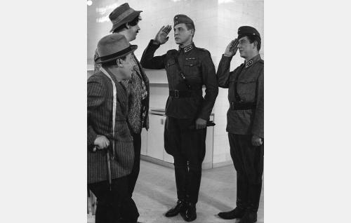 Kulkuri Masa Pikkarainen (Masa Niemi) ja hänen toverinsa Pikku-Aleksi (Armas Jokio) seurassaan komppanian komentaja kapteeni Jaakko Koivula (Kullervo Kalske) ja talousupseeri luutnantti Lennart Touhu (Arttu Suuntala).
