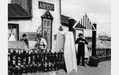 Hautausurakoitsija (Pentti Viljanen) liikkeensä edustalla. Vasemmalla hänen apulaisinaan Mauri Jaakkola ja Arto Mäkelä.