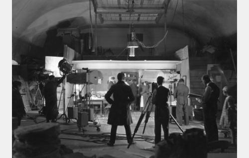 Korven perhettä (Axel Slangus, Waldemar Wohlström ja Olga Leino) kuvataan Vironkadun studiolla. Keskellä selin ohjaaja Erkki Karu, kuvaajana Eino Kari ja käsikirjoitus kädessään apulaisohjaaja Wilho Ilmari.