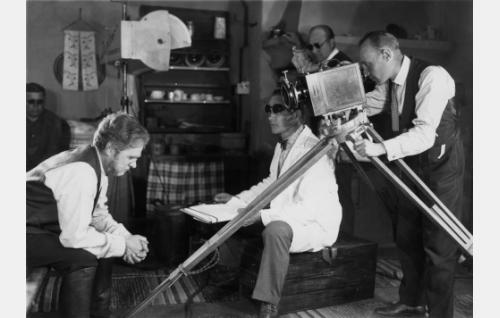 Matin isä (Waldemar Wohlström) mietteliäänä. Erkki Karu ohjaa, hänen takanaan apulaisohjaaja Wilho Ilmari ja kuvaajana on Eino Kari. Vasemmalla istuu studiopäällikkö Armas Fredman. Tummia laseja tarvittiin voimakkaiden valojen vuoksi.
