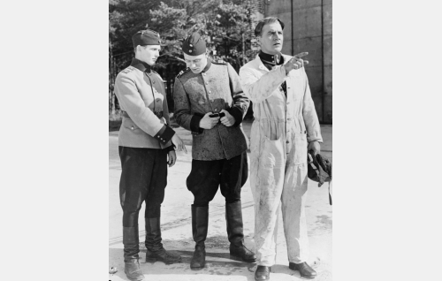Lähettikorpraali (Leevi Linko) huomauttaa ojaan kompastuneen ylikersantti Kalle Suulasen (Fritz-Hugo Backman) vaatteista tippuvan vettä, oikealla lentäjäluutnatti Jarmo Kurki (Joel Rinne).