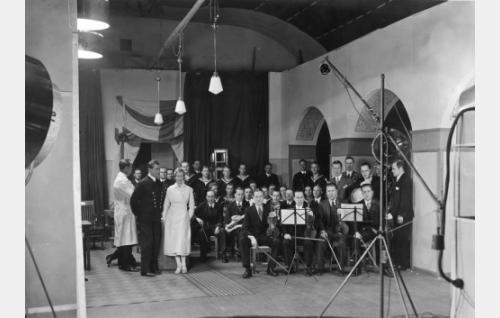 Suomi-Filmin Vironkadun studiolla valkotakkinen ohjaaja Erkki Karu, Georg Malmstén ja Kati Aspelin sekä merisotilaiden kuoro ja vahvennettu Zamba-orkesteri.