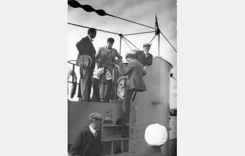 Kuvausryhmää sukellusvene Iku-Turson kannella, tornissa vasemmalla ohjaaja Erkki Karu.