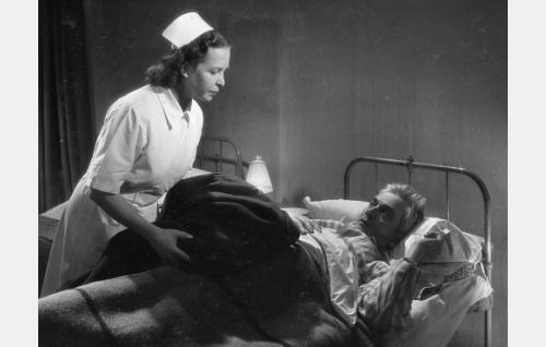 Sairaanhoitajatar (Sylvi Palo) ja portinvartija Saastamoinen (Paavo Jännes).