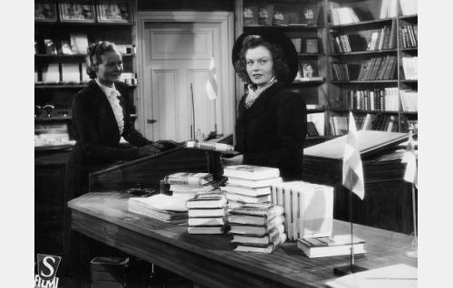 Kirjakauppias Anna Vainio (Emma Väänänen), hänen tyttärensä Virve (Irma Seikkula) ja uusi painos Martti M. Suomalan kirjasta Miehen kunnia.