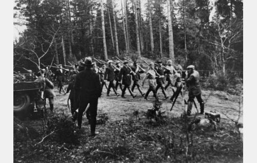 Työkuva: valkoisen puolen joukot etenevät. Oikealla kameroineen  kuvaaja Oscar Lindelöf, keskellä selin seisoo ohjaaja Kalle Kaarna.