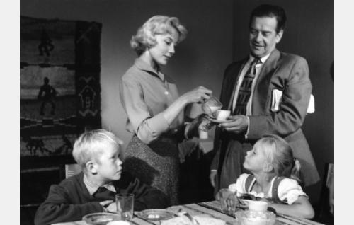 Onnellinen aamuhetki Koskisen perheessä, seisomassa Irma (Tea Ista) ja Eero (Kaarlo Halttunen), pöydän ääressä lapset Hannu (Hannu Halonen) ja Elina (Elina Halttunen).