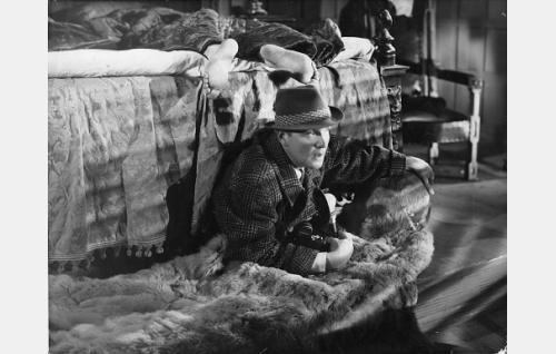 Sängyn alta ryömii valokuvaaja Seppo (Leo Lähteenmäki).