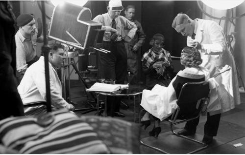Vasemmalla baskeripäinen kuvaajaa Theodor Luts, vieressään valkotakkinen kamera-assistentti Arvo Tamminen.Risto Orko nojaa ohjaajaanlakki päässään kameraan katsellen, kun Aarne Kuokkanen maskeeraa näyttelijä Maire Suvia. Huivi hartioilla ja neuletyö kädessä istuva Sirpa Tolonen kuuluu elokuvan naispuolisiin avustajiin.