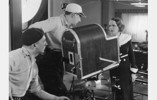 Risto Orko (keskellä) ohjaa Maire Suvia, vasemmalla baskeripäinen kuvaaja Theodor Luts. Uusi hieno ranskalainen Eclair-kamera on varustettu äänisuojauksella.