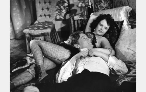 Allan Smith (Jussi Jurkka) usein nähtynä vieraana Madame Kraemerin salongissa.Ilotyttönä Mirja Mane.